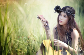 Pretty Girl In Grass Playing Guitar