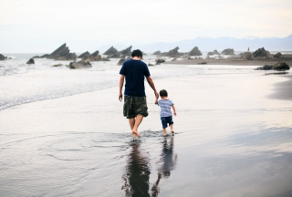 Father And Child Walking By Beach