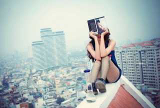 Girl With Book Sitting On Roof