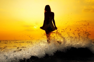 Girl Silhouette In Sea Waves At Sunset